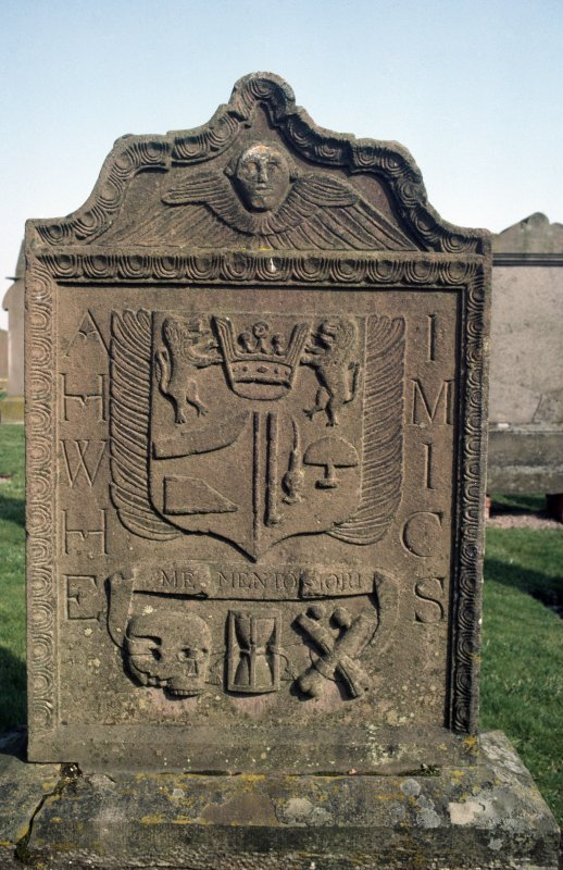 General view of gravestone with winged soul, shield and skull motif inscribed 'Memento Mori'.
