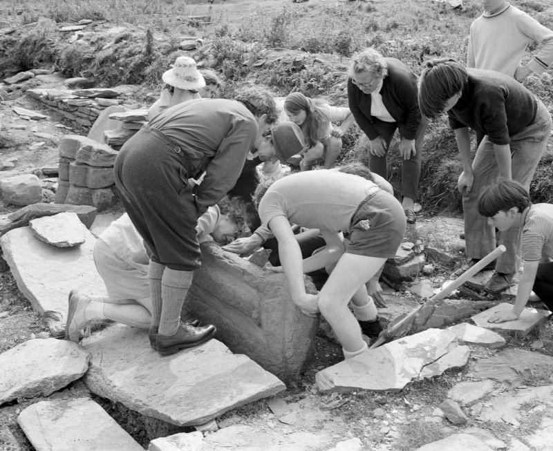 Veiw of the Middleton family, Annie Gillies and RCAHMS staff lifting a grave marker at Inchmarnock chapel in 1975, taken from the W.