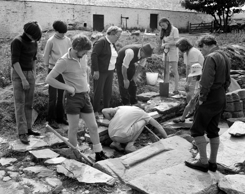 A working shot taken during the excavation of Inchmarnock chapel, and the visit of RCAHMS. In the foreground are (from left to right) S Scott, I Fisher and GD Hay (all of RCAHMS). In the background (f ...