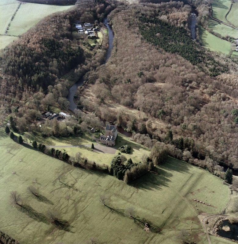 Oblique aerial view centred on the tower-house and earthworks with the stables and cottage adjacent, taken from the east south east.