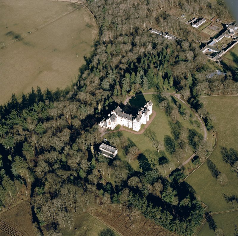 Oblique aerial view centred on the castle with farmsteading adjacent, taken from the SW.