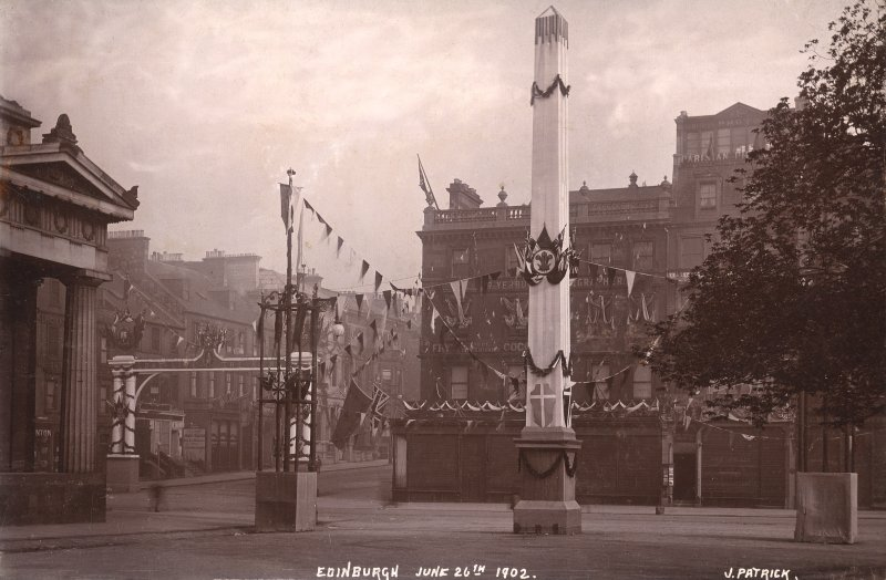Historic photographic view of obelisk by the Royal Scottish Academy, showing the street decorated on the coronation day of Edward VII.