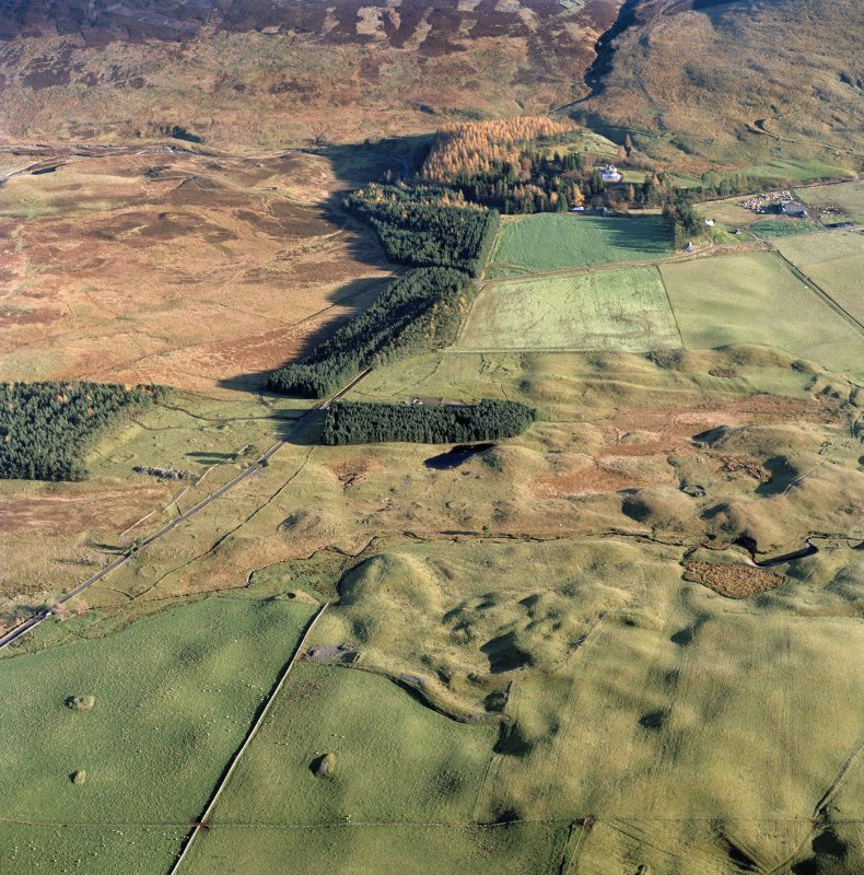 Oblique aerial view centred on the remains of hut-circles, small carins, banks, huts, farmstead, rig and buildings with cairn, building, rig and lodge adjacent, taken from the WNW.
