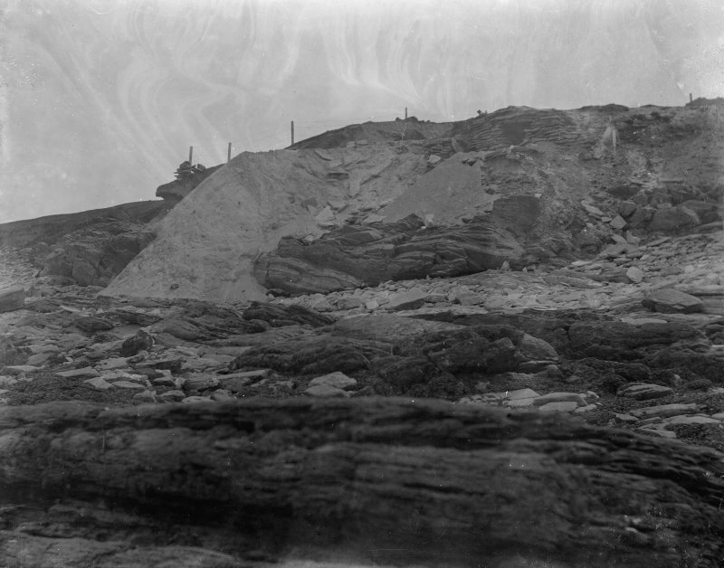 Excavation photograph: Spoil dumped over cliff, entrance to house 1 visible above.