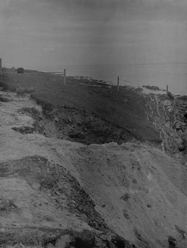 Excavation photograph: Spoil dumped over cliff, looking S.