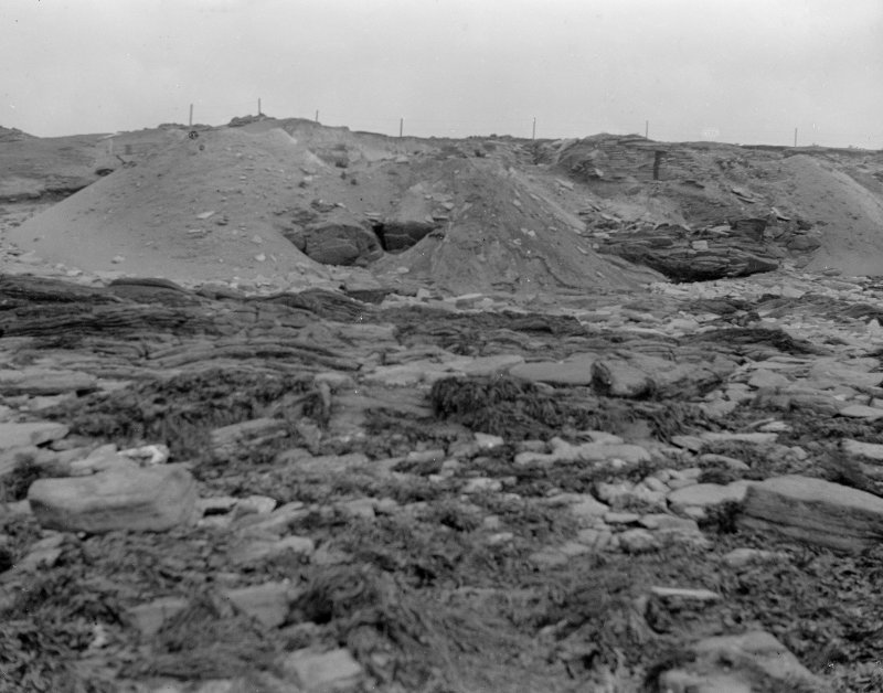 Excavation photograph: Spoil dumped over cliff.