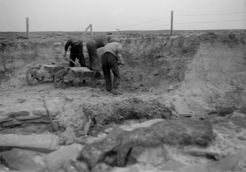 Excavation photograph: Workmen removing blown sand covering house 2. Copy negative 1995. Original print in Print Room.