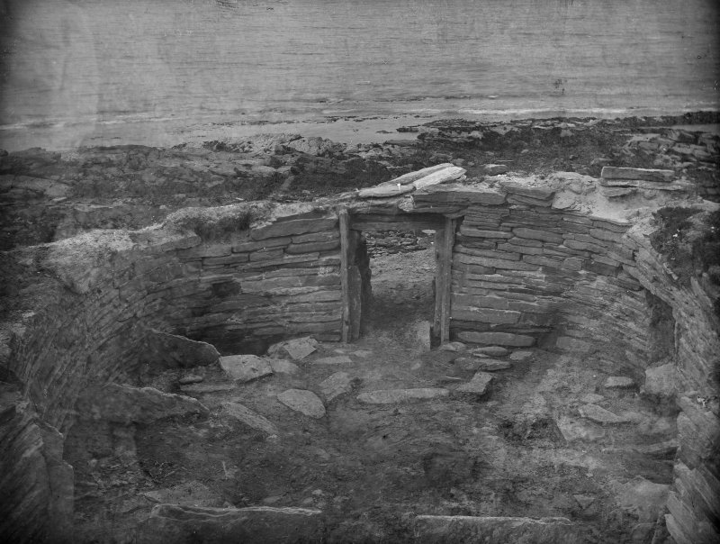 Excavation photograph: House 1, main entrance, partitions on stonebench to left.