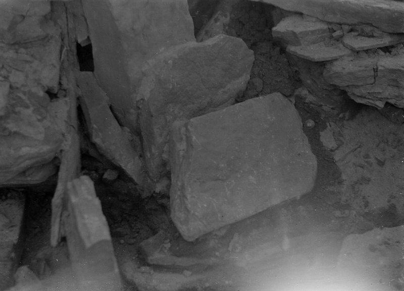 Excavation photograph: House 2, detail of tumbled stones in S. W. corner; Deliberate blocking of passage adjoining house 1 visible top.