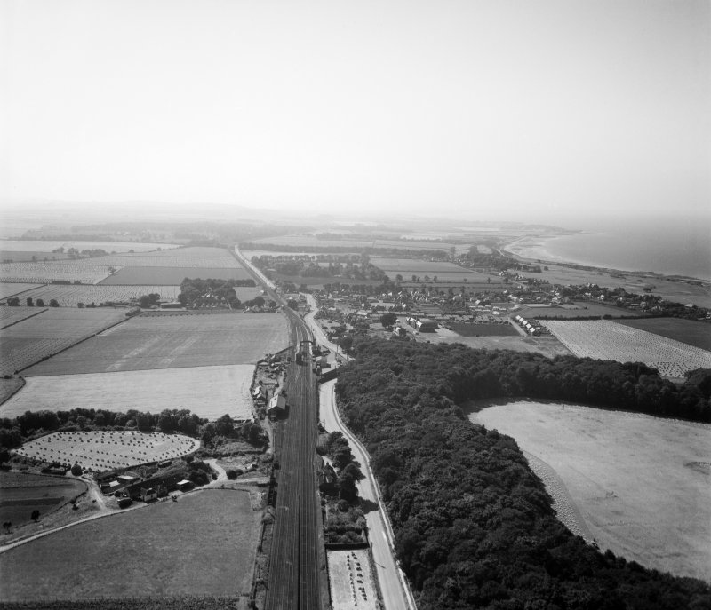 Longniddry, general view, showing Main Street and Fernyness Wood.  Oblique aerial photograph taken facing west.