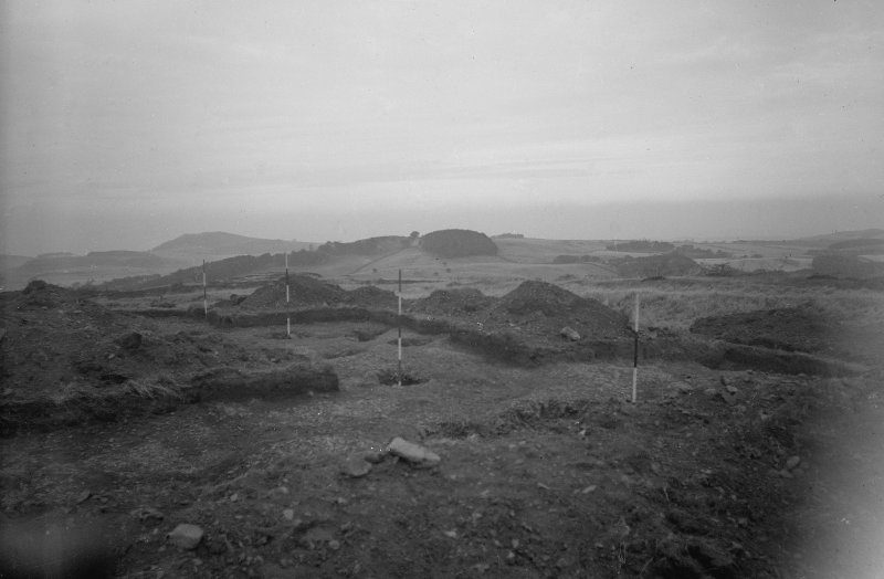 Cairnpapple Hill, photograph of excavation showing stone-holes (indicated by ranging poles) on E side.