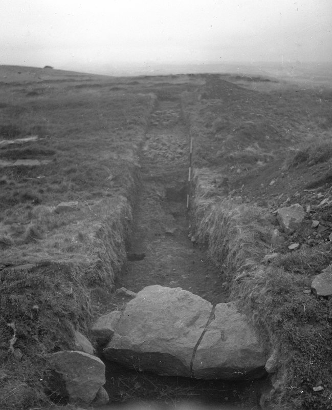 Cairnpapple Hill, photograph of excavation showing kerb stones of Period III cairn on W with henge ditch beyond.