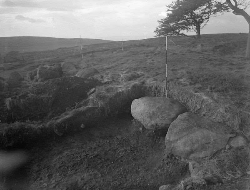 Cairnpapple Hill, photograph of excavation showing henge ditch on W, section Y with kerb stone of Period IV cairn.