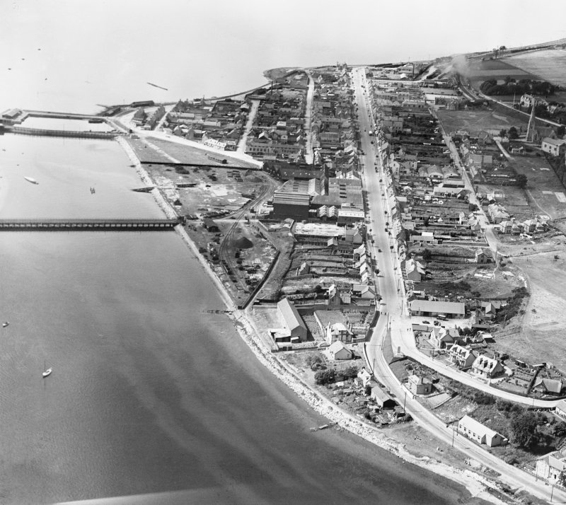 Invergordon, general view, showing High Street and Royal Naval Dockyard.  Oblique aerial photograph taken facing west.