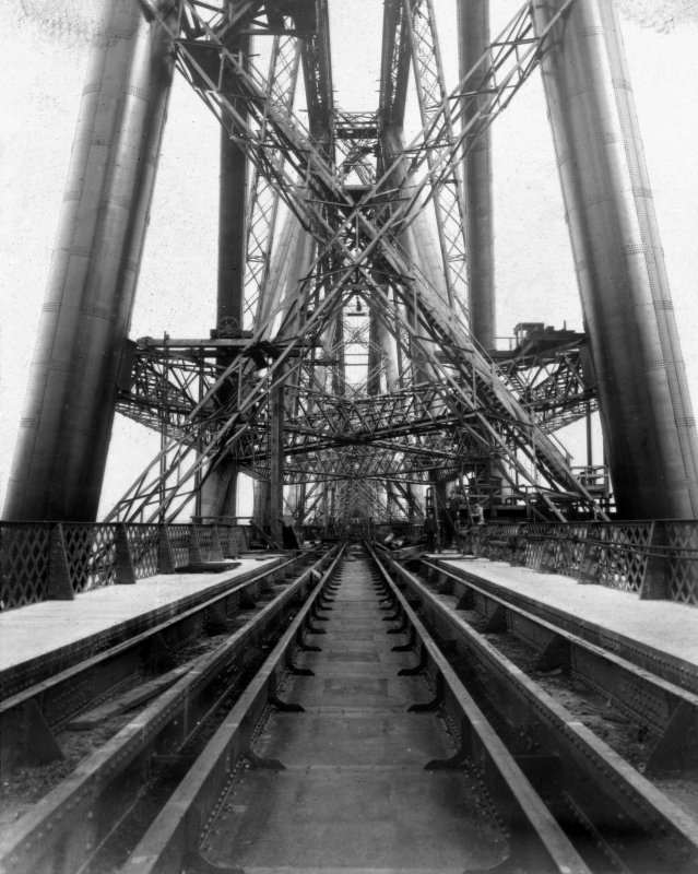 View along the tracks within the structure. Lantern slide.