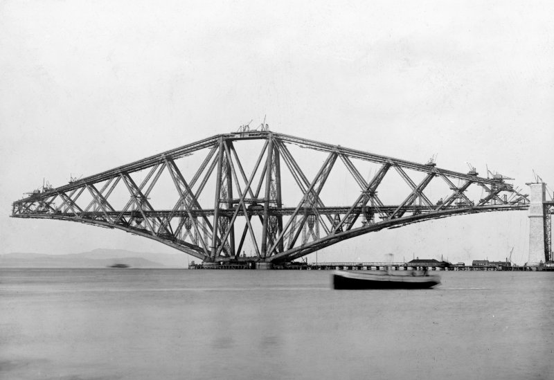 View of the Queensferry erection under construction seen from the West from the Firth of Forth. Insc. 'S. Cantilever. Forth Bridge. CF Cameron.' Lantern slide.