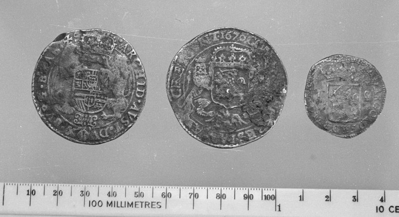 Silver coins from the wreck-site. (L-R: obverse of Philip IV ducaton, Brabant mint; obverse of United Provinces ducaton dated 1670; obverse of United Provinces 1-guilder coin dated 1706.)