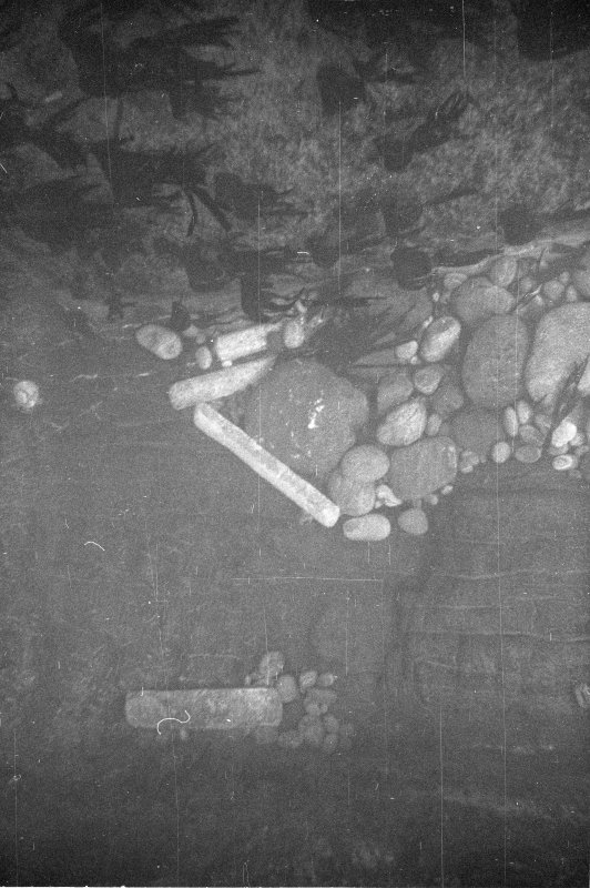 Four lead ingots lodged at the interface between the sides and fill of Gulley B. Note the short ingot lodged in a hollow of the gulley wall from where, it may be presumed, it has never moved since deposition.
