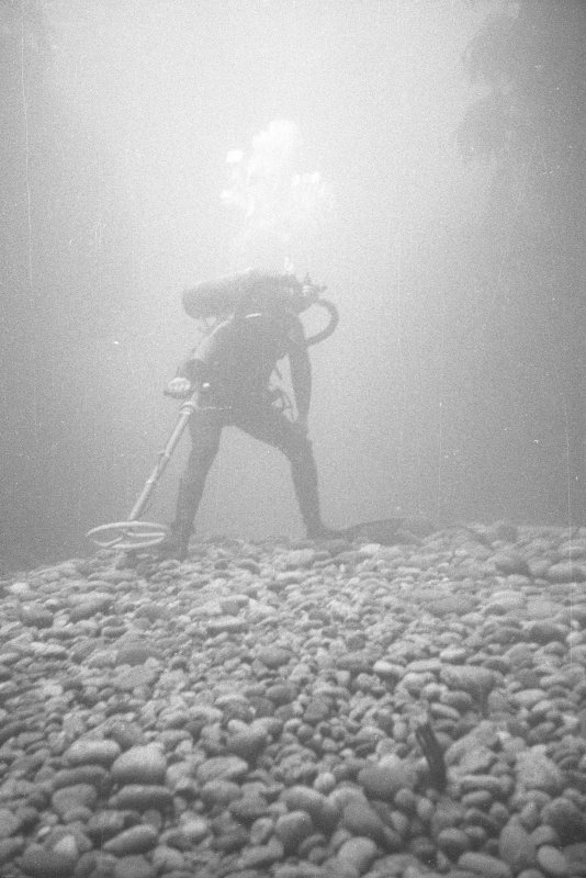 A diving archaeologist conducting a metal-detector survey in Gulley B. The rounded boulders in the foreground are typical of the fill of gulleys on the 				Adelaar wreck-site, indicative of the dynamic environment which moves them around. Weed growing on the vertical sides of the gulley is visible to left and right.