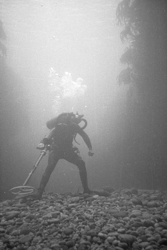 A diving archaeologist conducting a metal-detector survey in Gulley B. The rounded boulders in the foreground are typical of the fill of gulleys on the 				Adelaar wreck-site, indicative of the dynamic environment which moves them around. Weed growing on the vertical sides of the gulley is visible to left and right