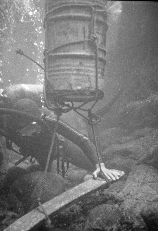 A lead ingot is lifted using an improvised flotation device made from an oil drum.