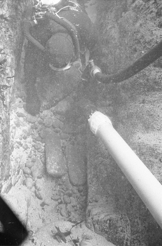 Excavating a narrow cleft in Gulley A with a suction dredge reveals two lead ingots.