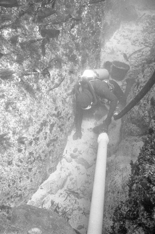Excavating a narrow gulley using a suction dredge. Note the bucket behind the archaeologist, used to carry away larger stones.
