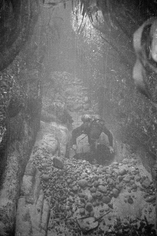 Excavating by bucket and shovel in Gulley A. Note the clear working face in the foreground and the stacked spoil lying behind the excavator. Beneath the overburden a coherent layer of iron concretion is being revealed.