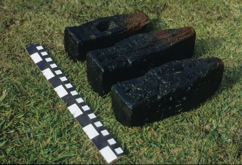 Three wrought-iron hammer-heads from the wreck-site, showing their hardened faces. Scale in centimetres and inches.