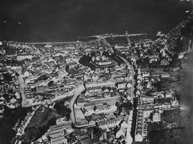 Rothesay, general view, showing Rothesay Castle and Union Street, Isle of Bute.  Oblique aerial photograph taken facing north.  This image has been produced from a print.