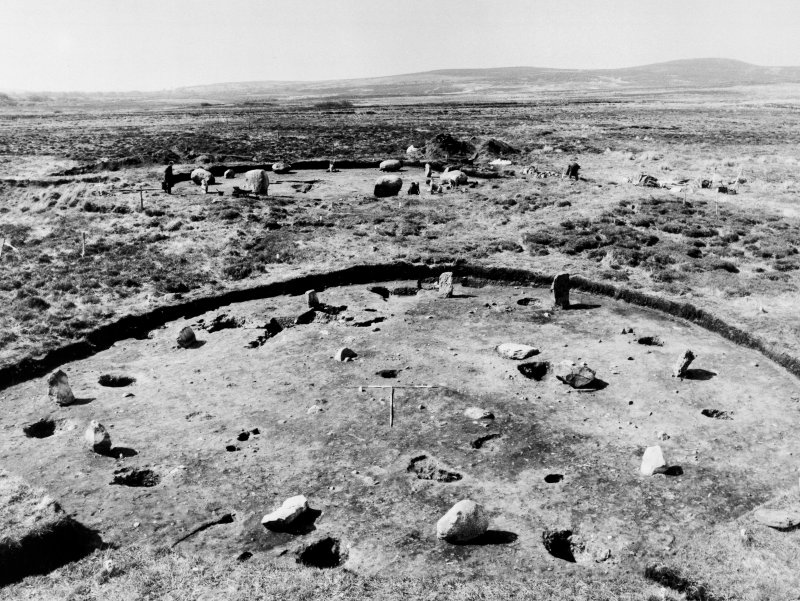 Excavation photograph. Stone circle XI in the foreground with circle I in the background, from the NE. At circle XI stone 4 (F120) is in the foreground with stone 5 (F121) lying out of position to its left. Posthole F110 (Burl's D) is between stones 4 and 5.
