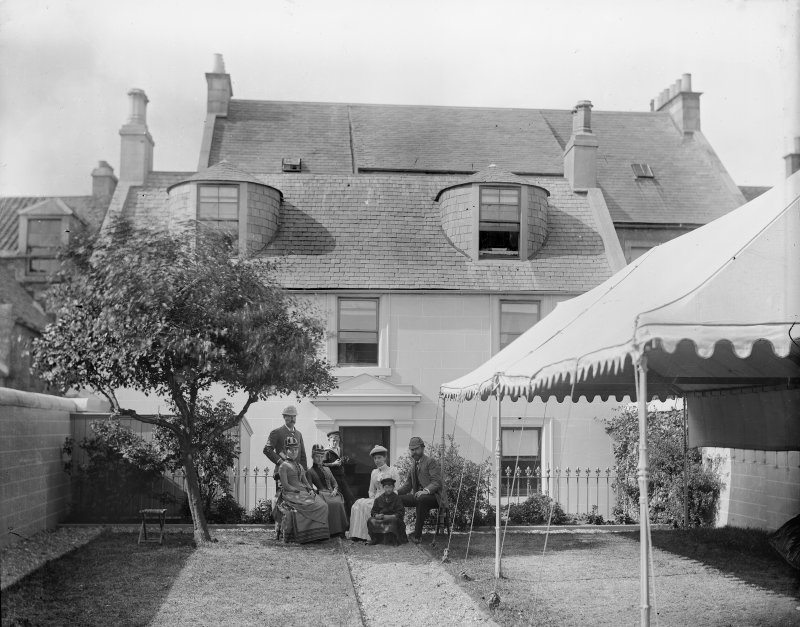 View of unidentified house with marquee and family group in garden.