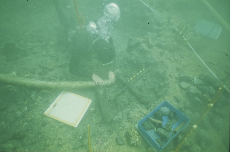 Paula Williams carrying out area excavation within the site grid. A wooden caulking mallet is being cleaned for recording - note her hand held over the nozzle for critical suction control. Drawing-board and finds box are to hand.