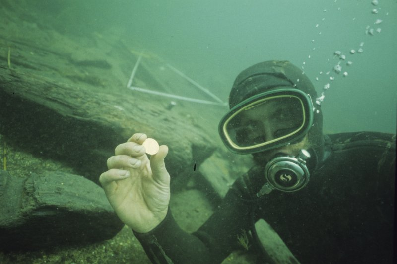 Tony Long displays a gold coin (D1001) recovered during excavation.