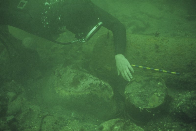 Paula Williams uncovers the lower part of a large ceramic jar (scale 1 foot), adjacent to a concreted iron gun.