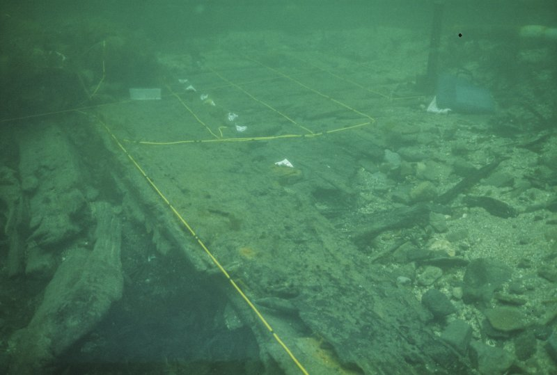 The main structural complex after excavation, comprising part of the lower starboard hull towards its aft end. Abrasion has ground the interior curvature to create a flat configuration, but the still-buried exterior face retains its original surface and contours. Individual components have been labelled for identification, while yellow datum lines provide a geometrical framework for recording.