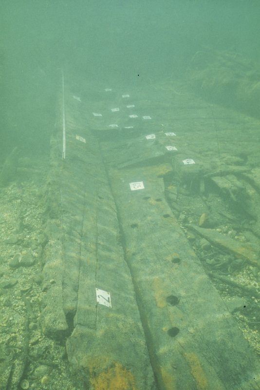 Top surface of the keel after the removal of the clamp timber which had covered it. Because of this protection, it is in pristine condition. Clearly visible is the diagonal capping of the scarph joint at an estimated position of one third of the way forward from the stern skeg. To its right is the well-preserved starboard garboard strake. Further forward are the chamfered frame-ends which were locked by the clamp timber, now removed. It is believed that this unconventional structural arrangement was a modification to allow the insertion of a new keel and lower timbers during a partial re-build of the vessel in 1678.