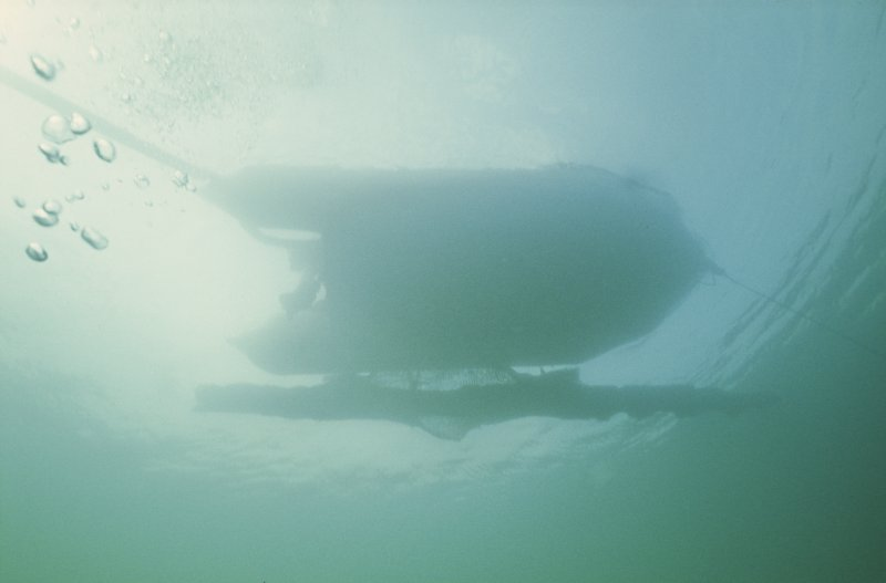 The cradled keel section suspended below the inflatable boat for transport ashore.