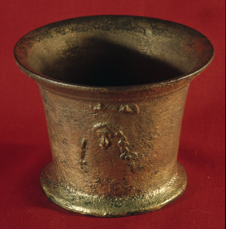 Copper-alloy apothecary's mortar (HXD 173) after cleaning and stabilisation, revealing a head with long hair and prominent eyes and nose, probably a caricature, perhaps of a Stuart monarch. Height 83mm, top diameter 108mm.