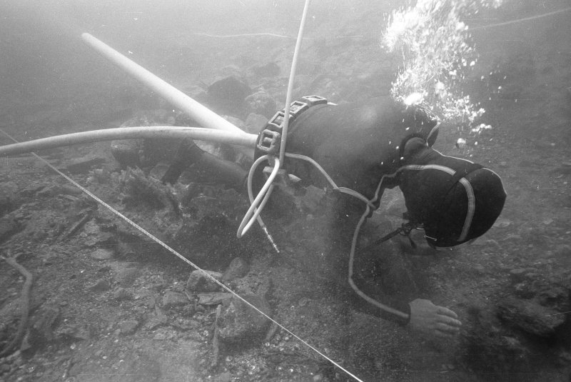 Archaeologist Colin Martin excavating with a water-dredge. (Jeremy Green)