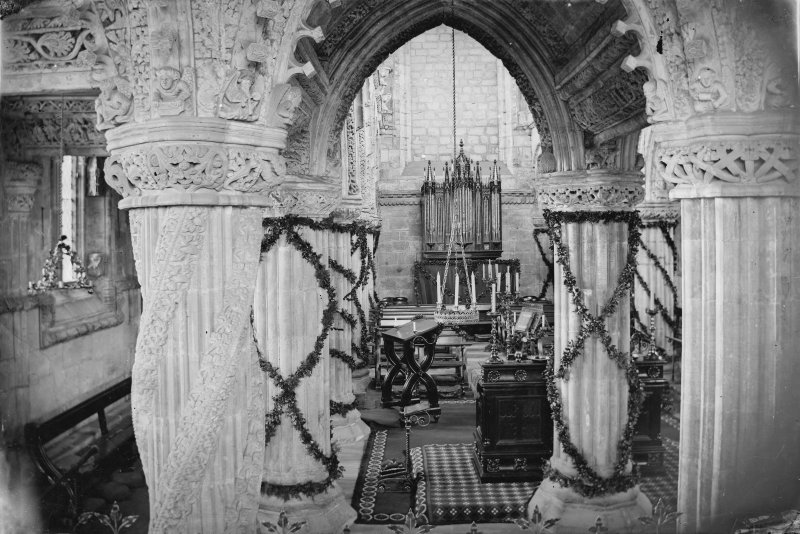 Interior view of Roslin Chapel with decorated pillars.