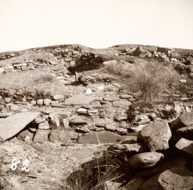 Photograph of part of a Broch with stones and grass