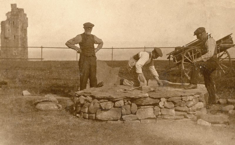 Scanned copy of photograph of John Nicolson and other men building a stone circle at New Keiss Castle gardens, with old Keiss Castle in the background
