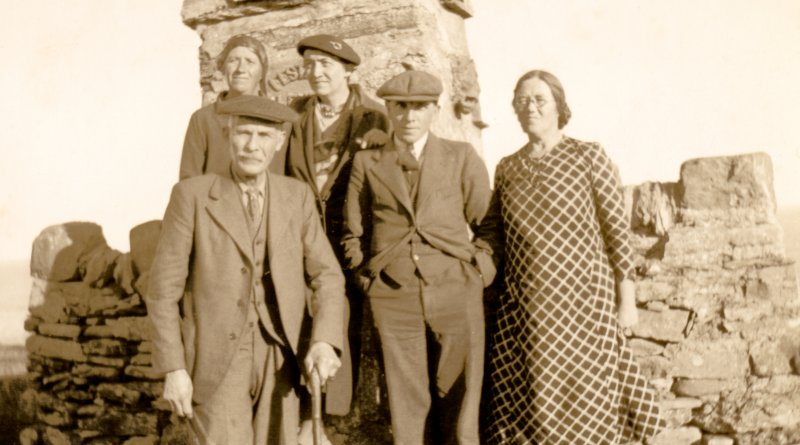 Scanned image of photograph of two men and three women standing in front of monument and stone wall at Nybster