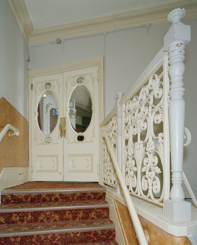 Interior.  Auditorium, W staircase to Circle, view showing double doors and balustrade