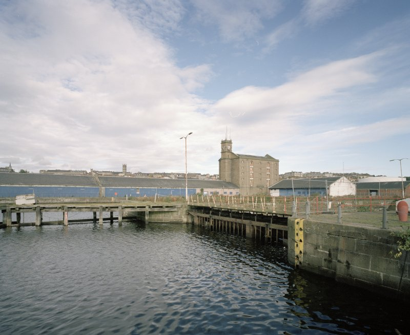 View from SSW showing entrance to the Dry Dock with transit sheds 26, 27 and the Harbour Warehouse in the background.