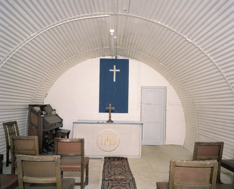 Interior view of church showing harmonium, altar and seating (hut 21)