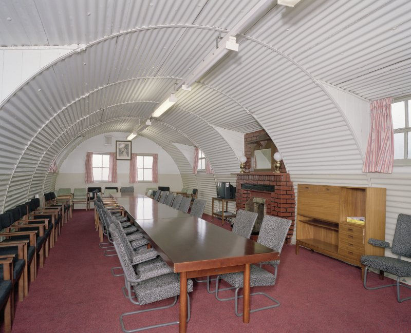 Interior view of officers mess, conference room (hut 27) showing meetings table, seating and fireplace