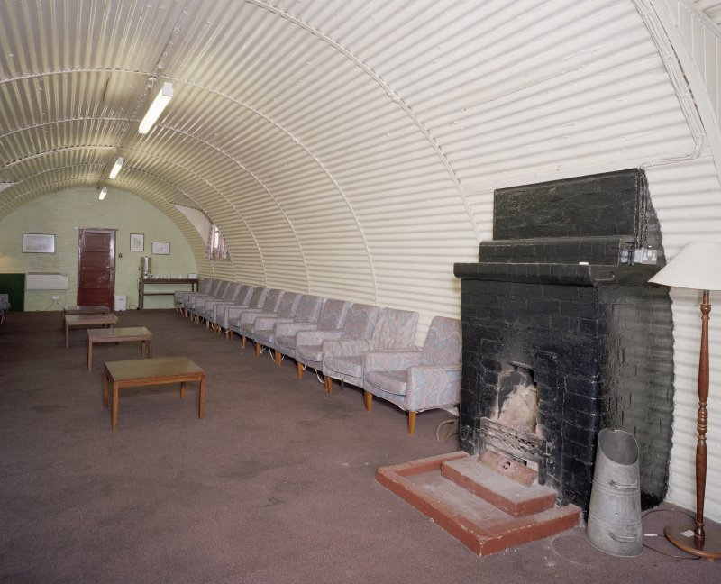 Interior view of sergeants mess, lounge showing brick built fireplace and seating arrangement