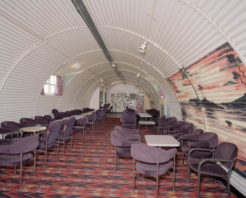 Interior view of NAAFI (hut 65) showing seating and table arrangement with wall paitings/cartoons of corrugated iiron walls